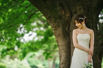 木の前に立つウェディングドレスを着た女性