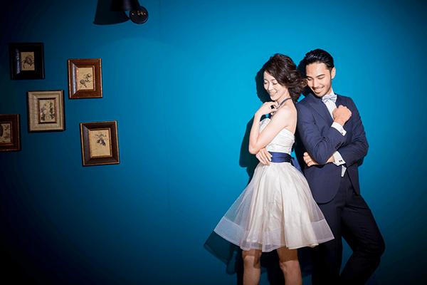 ブルーの壁を背景にポーズしている新郎新婦