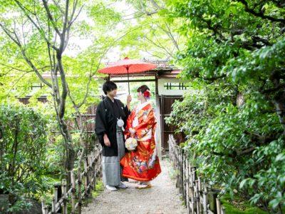 和傘を持って笑い合う新郎新婦